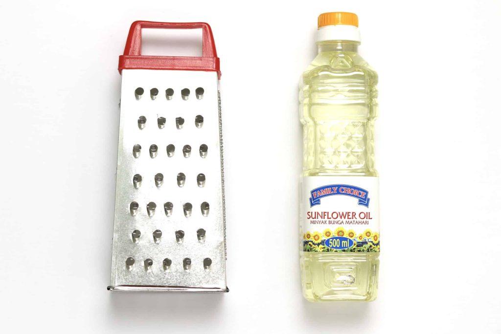 A cheese grater lightly coated in sunflower oil, alongside a bottle of sunflower oil.