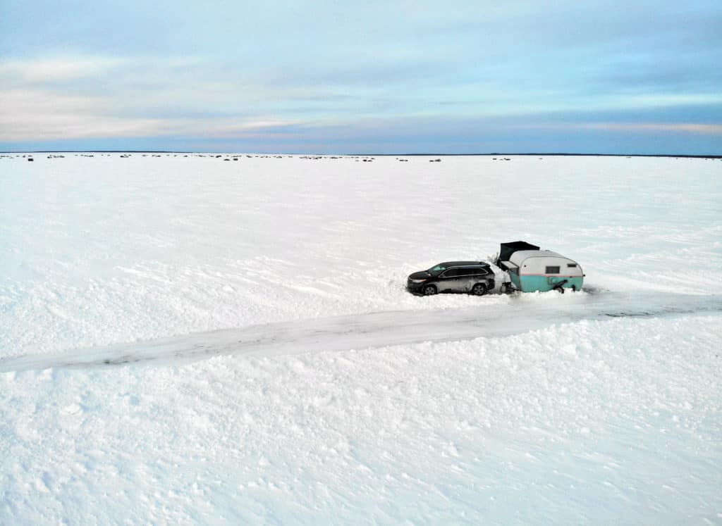 Aerial view of fish house camper on Lake of the Woods ice road.