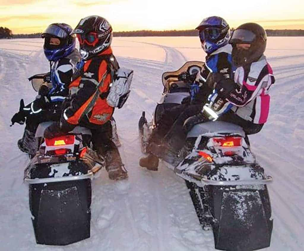 Two couples snowmobiling on a groomed trail.