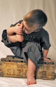 Kind riecht an Fuß
