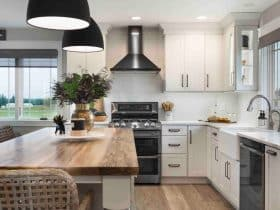 all white cabinet open space modern farmhouse kitchen and dining room combo with black appliances