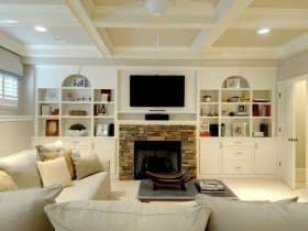 combination of fieldstone fireplace and polished white built-in shelves around