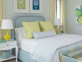 a sapphire bed with a stone headboard combine seamlessly with yellow bedside lamps