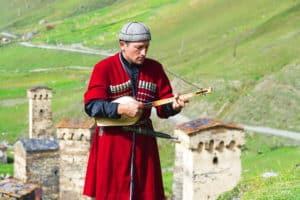 Georgisches typisches Kostüm mit den mittelalterlichen Türmen von Ushguli