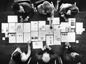 Business people analyzing cost savings by looking at papers spread out on table