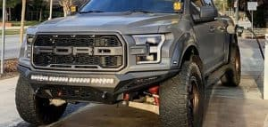 gray ford f150 with shocks in street