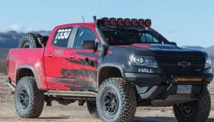 red chevy silverado with shocks in mud background