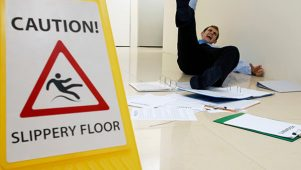 Wet floor sign with a business person slipping