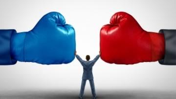 Ein Mann steht zwischen zwei Boxhandschuhe.