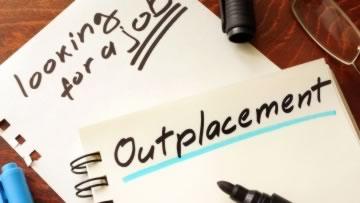 Das Wort Outplacement steht auf einem Notizzettel.