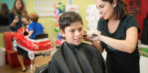 older boy getting his hair cut at pigtails & crewcuts