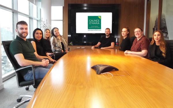 The Caunce O'Hara Schemes team sat around a boardroom table.