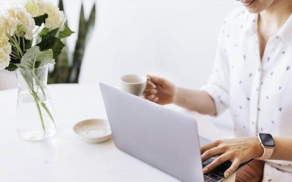 Building a freelance copywriting business - freelance copywriter working on laptop and drinking a coffee