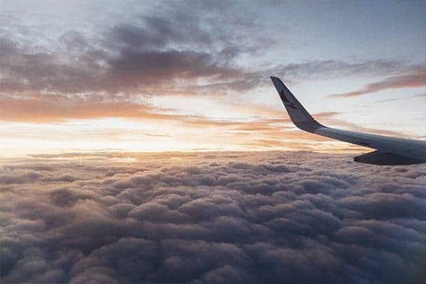 The wing of an aeroplane in the clouds at sunset