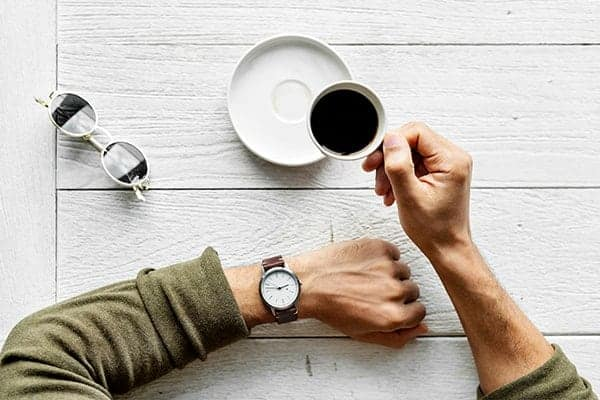 Birds eye view of a freelancer's hand holding an espresso coffee and other arm wearing a watch.