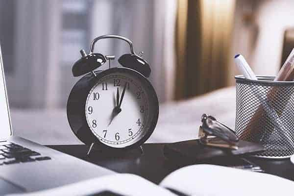 How to manage several freelance clients at once - Black alarm clock with white face on work desk