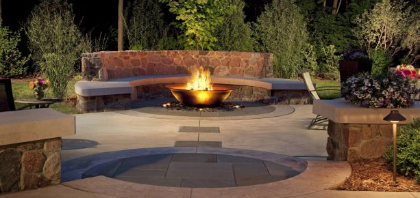 trendy granite fieldstone paver patio with semicircle bench around a fire bowl pit