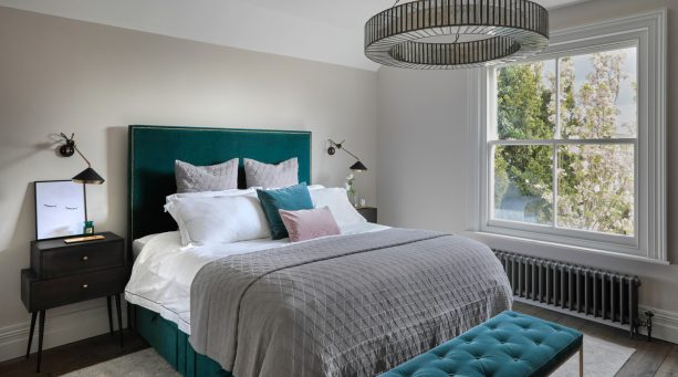 gray dominated mid-sized transitional bedroom with teal bed