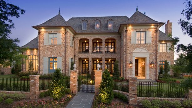 french country brick house with shutters in a combination of light gray green color