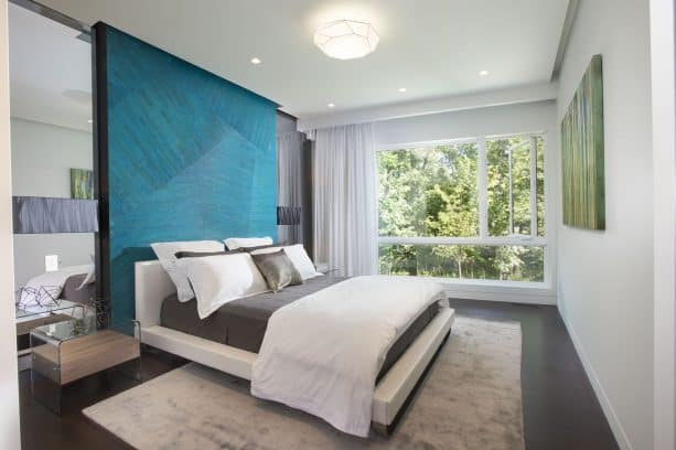 a contemporary bedroom with charcoal bed and teal headboard