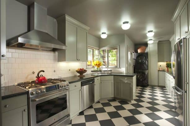 a handsome mix of checkered tile and sage green cabinets in a retro kitchen
