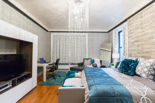 a large modern master bedroom with the ash-gray wall, the combination of fossil and cobalt bed with the teal carpeted on the floor