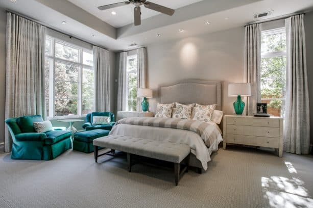 large transitional master bedroom with gray-dominated paintings and teal comfortable sofa