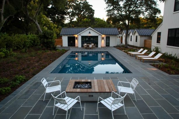 a fire pit seating area and patio with bluestone paver around a pool
