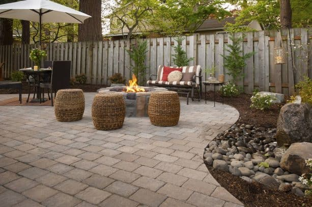 a relaxing patio with a circular stone fire pit and roman cobblestone paver
