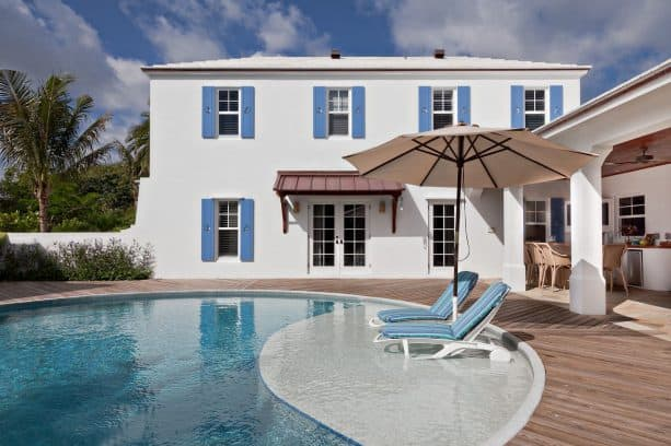 white mediterranean house highlighted by blue shutter, tropical pool & decking