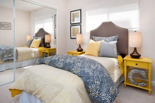 combine a blue-yellow comforter, a blue pillow, and sun porch bedside tables for a homey bedroom