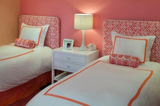 create a serene bedroom with a rosy blush wall and matching pink headboards on white beds
