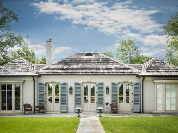 mid-size traditional white house with external blue shutters