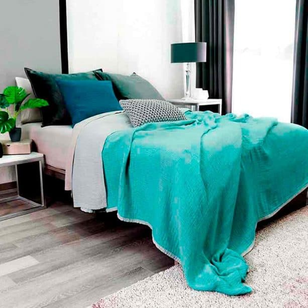 a small trendy master bedroom with gray wall and floor combined with teal bed cover
