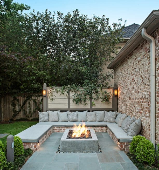 bluestone paver patio with bench seating around a square fire pit table