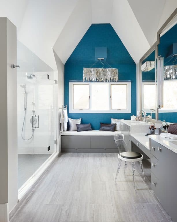 a blue wall and gray cabinets are perfect for a glamour transitional bathroom