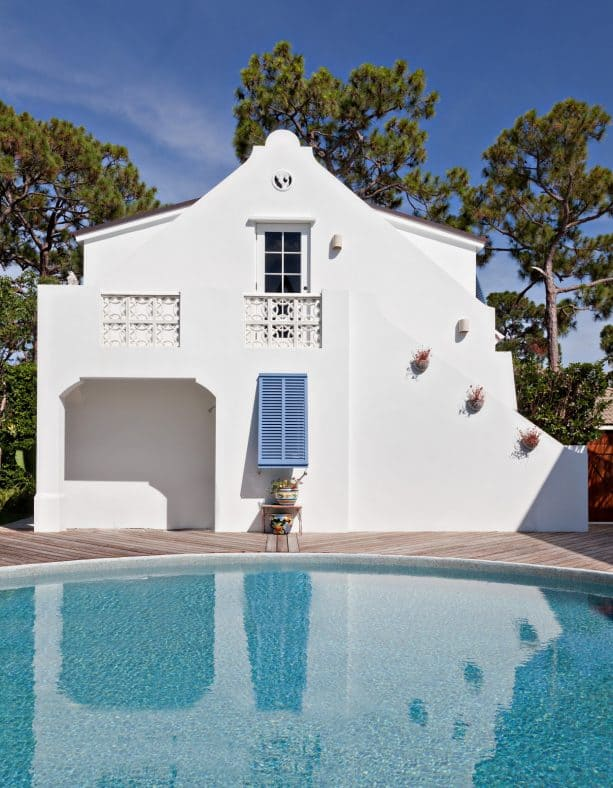 two-story tropical house in white with a decorative blue shutter installation