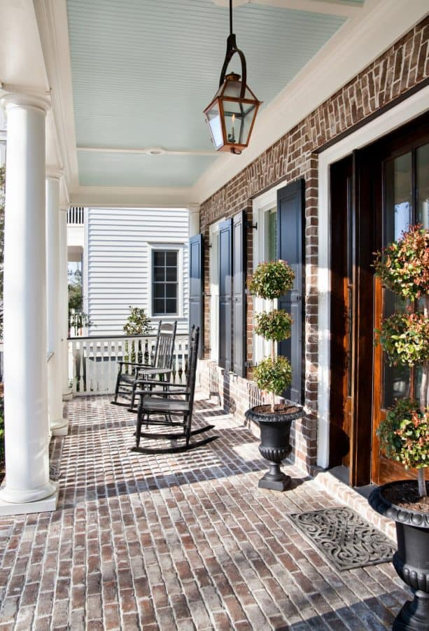 elegant porch of a brick house with charleston green shutters