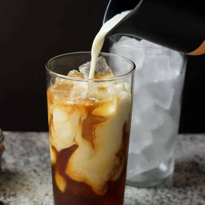 milk pouring into a glass of iced coffee with a container of ice behind it