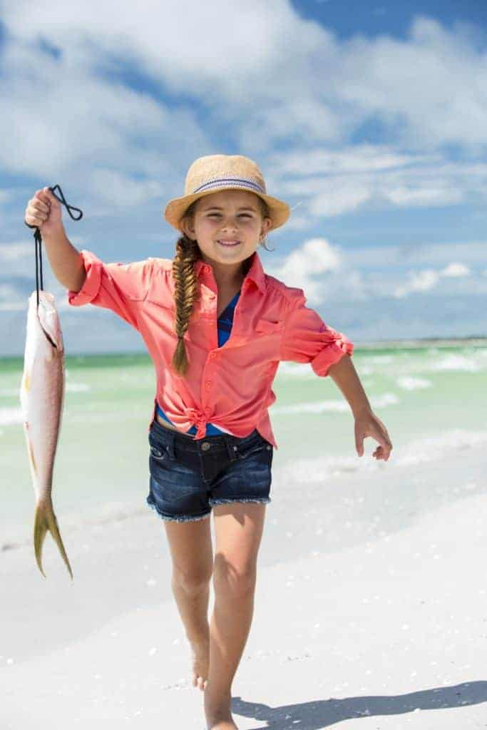 Kid on the beach with a fish.