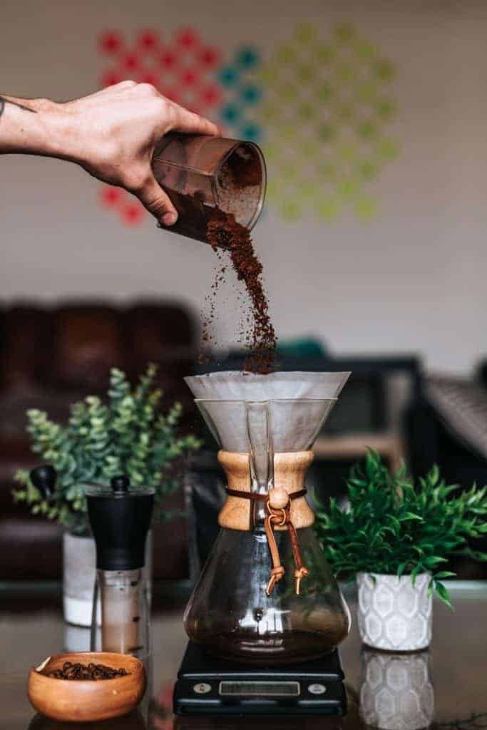 hand pouring coffee grounds into a chemex pourover coffee maker with decorative elements beside it to indicate gift ideas