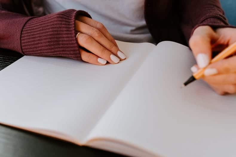 Close up of a notebook with a woman's hands writing - make a plan for anxiety at night.