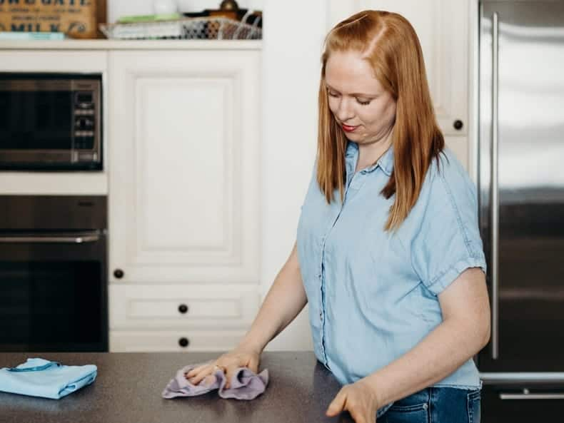 Woman wiping countertop with Norwex cloth