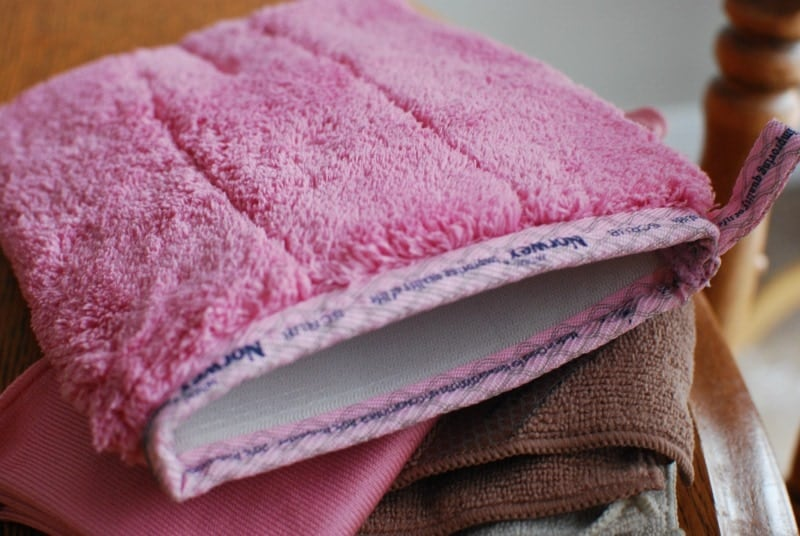 pink norwex scrub mitt on a stack of other norwex cloths
