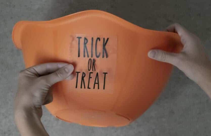 placing adhesive vinyl design on Halloween candy bowl