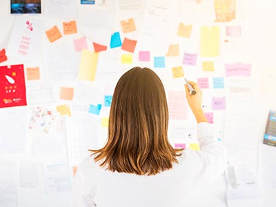 Overwhelmed Business Woman Trying to Understand VoIP With Post It Notes on a Board in Front of Her