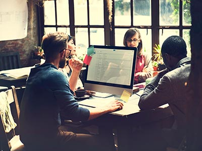 Four Employees of Startup Company Meeting in Small Office to Discuss Business Communication Solutions