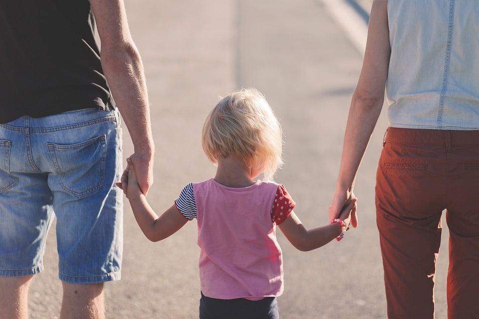 Mutter und Vater halten ihr Kind an den Händen