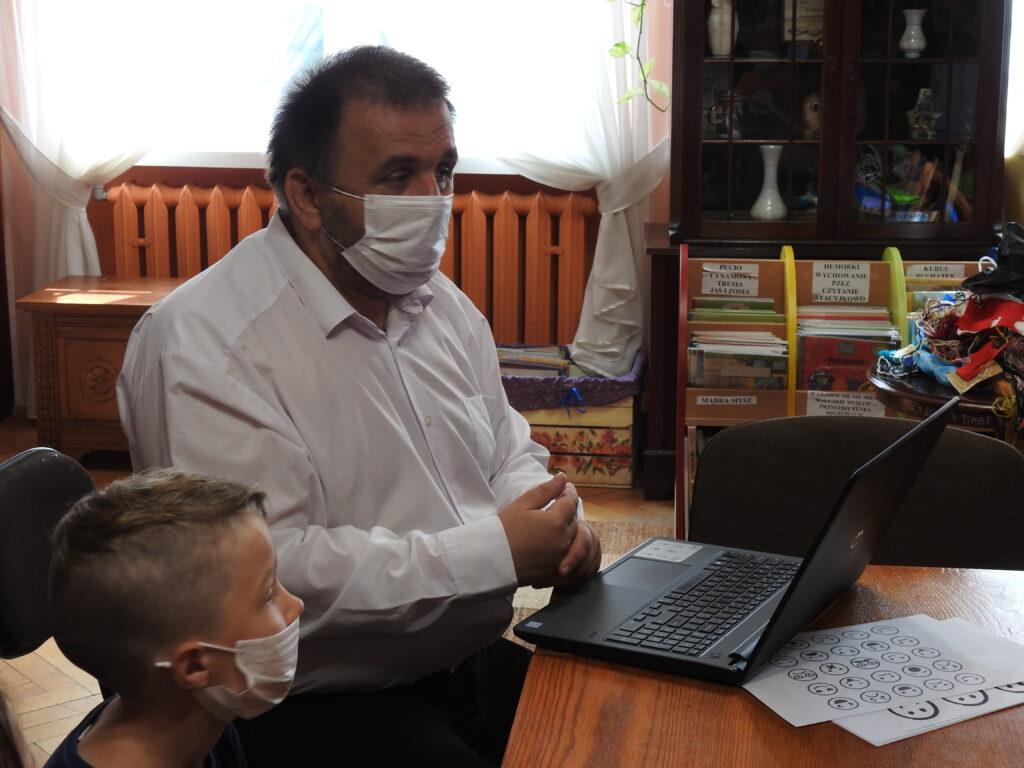 Dorosła osoba patrzy e ekran laptopa. Obok dzieci dziecko.