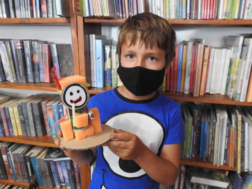 Dziecko w masce, w tle regały z książkami, w ręce trzyma figurkę wykonaną z różnych materiałów.